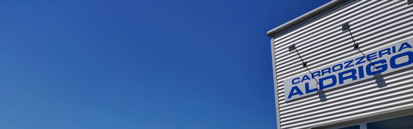 Insegna Carrozzeria Aldrigo sul capannone con cielo blu di sfondo
